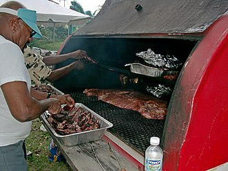 "Barbecue - A barrel-shaped barbecue on a trailer. Pans on the top shelf hold hamburgers and hot dogs. The lower grill is being used to cook pork ribs and ""drunken chicken""."