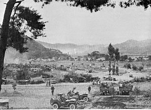 Trucks depart for a distant battlefield in the mountains where explosions can be seen