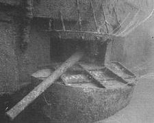 Unterwasserfoto einer Waffe, die aus einer Öffnung an der Seite eines versunkenen Schiffes herausragt.