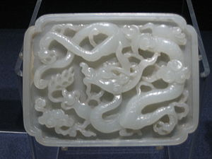 A Yuan Dynasty jade belt plaque featuring carved designs of a dragon.