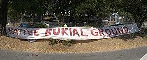 "University of California, Berkeley oak grove controversy - Berkeley Memorial Stadium oak grove and protest banner reading ""Native Burial Grounds"""