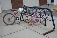 An open A-frame of thick steel tubing. Attached underneath the crossbar is a spiral of thinner metal tubing. It is painted blue, but much of the paint has flaked off, leaving rust. A mountain bike and a child's bike are parked in it and two abandoned D-locks hang from it. In the background is a brick-and-plaster building and behind the rack, to the right, is a car parking space.