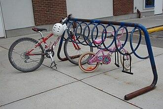 Открытая А-образная рама из толстых стальных труб. Под перекладиной прикреплена спираль из более тонкой металлической трубки. Он окрашен в синий цвет, но большая часть краски отслоилась, оставив ржавчину. В нем припаркованы горный велосипед и детский велосипед, а с него свисают два заброшенных D-образных замка. На заднем плане - кирпично-гипсовое здание, а за стойкой справа - место для парковки автомобиля.