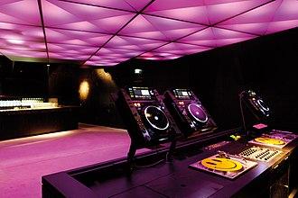 CDJ - A DJ setup in a nightclub, consisting of three CDJs, turntables and a DJ mixer