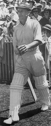 Black and white image of a man in cap and white cricket kit with batting pads and gloves on, walking onto a cricket ground. A number of spectators are in the background behind a fence.