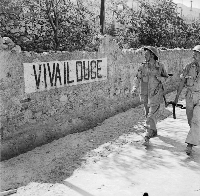 British soldiers smile at a 'Viva Il Duce' slogan on a wall in Reggio, Italy, September 1943. NA6230