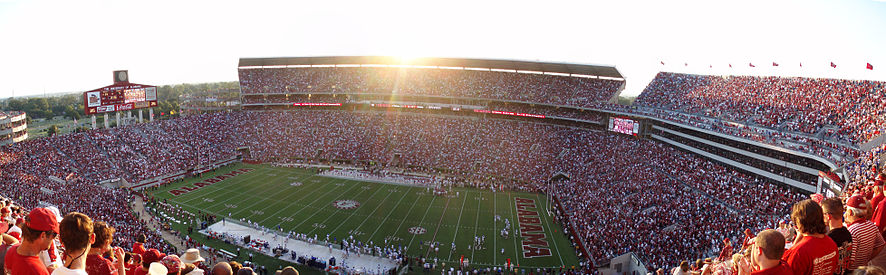 A setting sun with the interior of Bryant-Denny Stadium full of fans and players on the field.