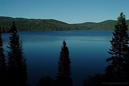A large lake under blue skies surrounded by forested hills with steep slopes under a clear blue sky