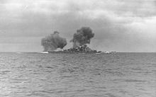 Black-and-white photograph of a warship firing the guns. Two columns of dark smoke drift from the ship