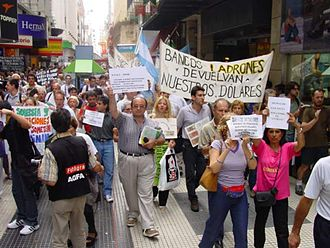 "Corralito - A protest against the banks in 2002. The large sign reads ""Thieving banks - give back our dollars""."