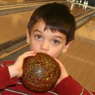 Bowling ball - Child holding a duckpin bowling ball, illustrating its small size.