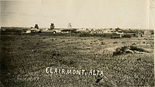 A black and white image of a rural town with three elevators and town buildings from an adjacent hay field