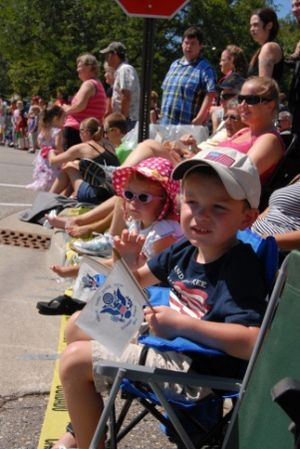 """Coast Guard City - Children wave the flag of the United States Coast Guard during the Grand Haven, Michigan Coast Guard Festival Parade in 2013. In 1998 Grand Haven became the first city designated a """"Coast Guard City."""""""