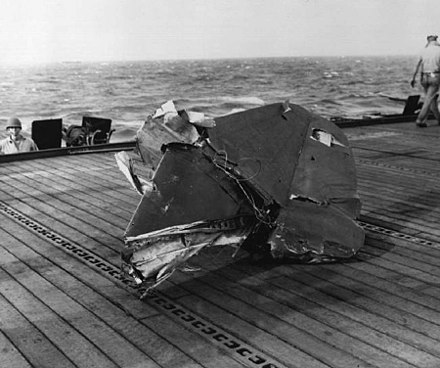 "Starboard horizontal stabilizer from the tail of a ""Judy"" on the deck of USS Kitkun Bay. The ""Judy"" made a run on the ship approaching from dead astern; it was met by effective fire and the plane passed over the island and exploded. Parts of the plane and the pilot were scattered over the flight deck and the forecastle. D4Y tail kitkun.jpg"