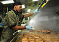 Defense.gov News Photo 110124-N-9793B-024 - Seaman Diante A. Johnson prepares pork chops in the ship s galley for the crew aboard the guided-missile cruiser USS Anzio CG 68 underway in the.jpg