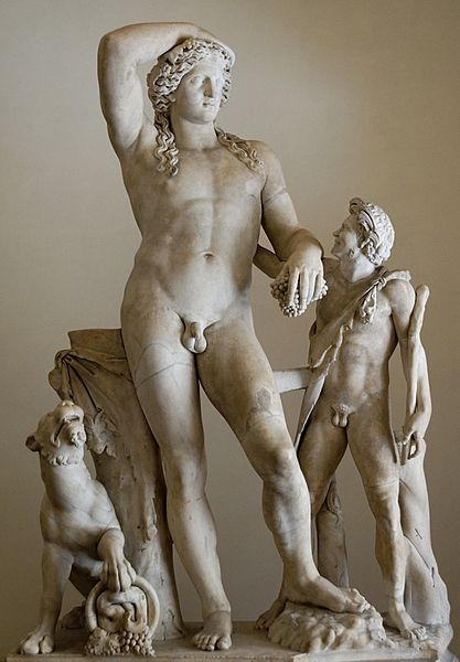 A marble statue of two men, one tall (this is Dionysus, on the left), drunk and with one hand flung back behind his head; he leans on a tree strump as a smaller younger man, a satyr, reaches up to try and help.