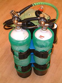 The rear view of a set of twin independent cylinders strapped to a jacket harness, each with a scuba regulator fitted.