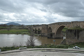 Photo of an old arched stone bridge over a river. There is a mountain in the distance