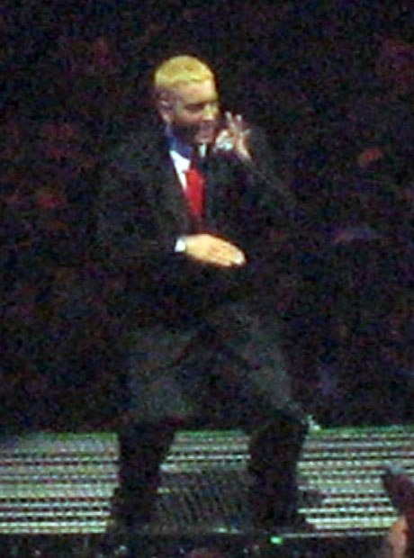 Eminem onstage, with blond hair and wearing a suit