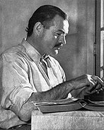 A black and white photo of Ernest Hemingway seated at a typewriter
