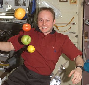 Expedition 9 - Edward M. (Mike) Fincke, Expedition 9 NASA ISS science officer and flight engineer, is pictured near fresh fruit floating freely in the Zvezda Service Module of the International Space Station. (NASA)