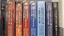 Seven thick large paperback books, each with different Japanese writing on the binding, wrapped in plastic, sitting on a shelf in a row