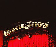 "Image of a concert stage. It is written ""GIRLIE SHOW"", in yellow, above red curtains, as flashes of lights illuminate the stage."