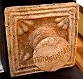 "Glazed (originally blue) door plaque with boss. The Elamite cuneiform inscription reads ""Palace of Untash-Napirisha, King of Elam"". 13th centiury BCE. From Choga Zanbil, Iran. British Museum.jpg"