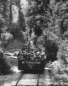 A single open railroad car, on a single rail track that twists and turns through a forest. The car is carrying about 30 passengers, all of whom are wearing hats.
