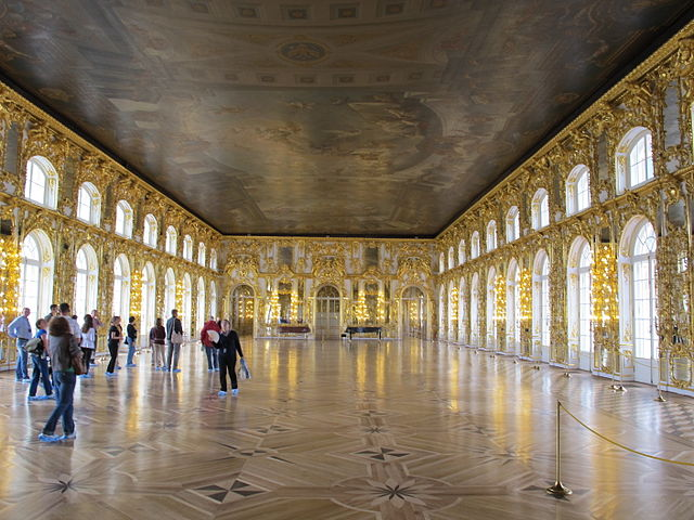 A huge room with a parquet floor, goldleafed walls ornamentation, and a painted ceiling