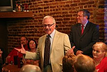 Barr stands in front of a brick wall in a vanilla suit, with his arms stretched to convey a point, before the small crowd around him