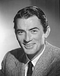 Black and white publicity photo of Gregory Peck—a white man with dark eyes and straight hair, smiling and wearing a suit, around 32 years of age—in 1948.