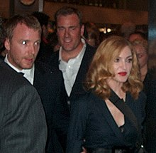Madonna and Guy Ritchie in black dress, looking to their left.