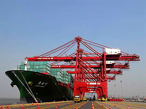 Maritime transport - Harbour cranes unload cargo from a container ship at the Jawaharlal Nehru Port in Navi Mumbai, India.