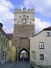 View of a street of old buildings, the largest of which is a tall clock tower with an archway