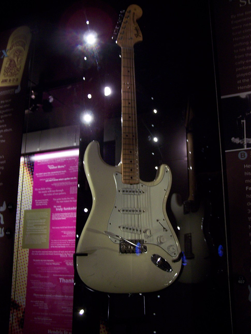 A color photograph of a white Fender Stratocaster guitar