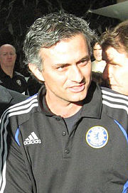 The head and upper torso of a man with black, greying hair. He is wearing a black polo shirt with the blue Chelsea F.C. crest on the left breast and a white logo of the Adidas sponsor on the right breast. Three white stripes are visible on the shoulder.
