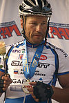 male cyclist standing on a winner's podium