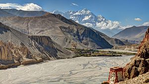 Upper Mustang - Kali Gandaki riverbed in Nepal's Upper Mustang. View from Thsele down to the Kali Gandaki river and the fields of Chusang village, with Nilgiri's steep north face.