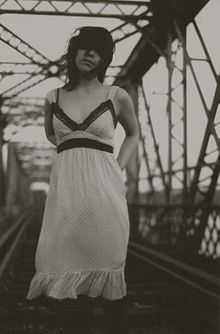 A sepia image of a woman standing on a bridge with railway tracks.