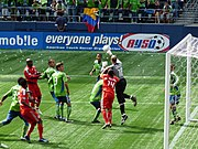 Several players in red uniforms and green uniforms in front of goal with a goalkeeper in black leaping with his hand hitting a soccer ball