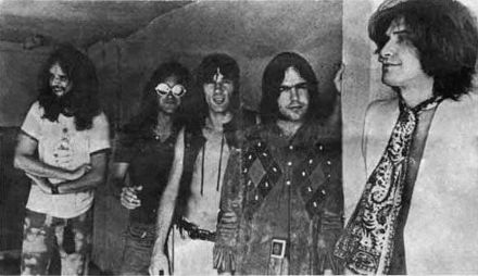 Five smiling men in a row, diagonal to camera angle. The man on the left (farthest to the back) has very long hair and a full beard; he wears a white T-shirt and tie-dyed pants. Next to him, Dave Davies, also with very long hair, wears reflective sunglasses, a black short-sleeved shirt and jeans. In the middle, Mick Avory wears an unbuttoned leather vest and white pants. The man to his right wears a heavy, probably brown leather jacket with a design that is possibly Native American. On the far right, in front, Ray Davies wears a giant paisley kerchief knotted like a tie, over a white jacket.