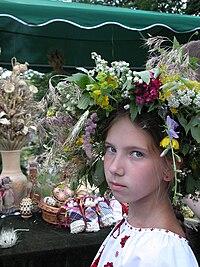 Dziewczynka w wianku z żywych kwiatów na głowie