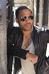 A colored photograph of Lenny Kravitz, wearing sunglasses and a black jacket.