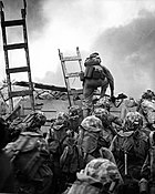 photograph of Marines waiting to climb the seawall at Inchon, while one Marine centered is bent over while dismounting the top of a ladder
