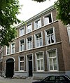 foto van Huis met lijstgevel en poort, uitspringende t.o.v. het vorige.