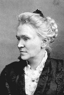 A faded monochrome photograph portrait of a woman turned to the left, facing further left, wearing a dark coat closed with a floral brooch, over a white blouse with a lacy collar, the woman's blond hair held up in a bun on the back of her head, with a dark hair comb standing vertically in the bun