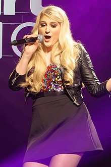 Meghan Trainor performing in a colorful top, black jacket and skirt.