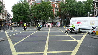 Emergency vehicle equipment in the United Kingdom - Six Metropolitan Police Service motorcycles driving with the blues and twos on. They can be seen breaking a number of normal traffic rules. Each motorbike has driven through a red light, and the motorbike on the far right can be seen driving on the wrong side of the road and passing on the right of a keep left sign.