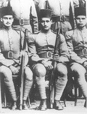 To sittende menn i militæruniform og iført fez-hatter